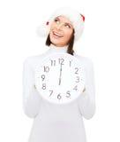 Mulher no chapéu do ajudante de Santa com o pulso de disparo que mostra 12 Fotografia de Stock