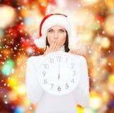 Mulher no chapéu do ajudante de Santa com o pulso de disparo que mostra 12 Imagens de Stock