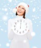 Mulher no chapéu do ajudante de Santa com o pulso de disparo que mostra 12 Fotografia de Stock Royalty Free