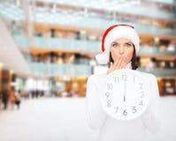 Mulher no chapéu do ajudante de Santa com o pulso de disparo que mostra 12 Fotos de Stock Royalty Free