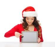 Mulher no chapéu do ajudante de Santa com PC da tabuleta Foto de Stock