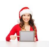 Mulher no chapéu do ajudante de Santa com PC da tabuleta Fotografia de Stock Royalty Free