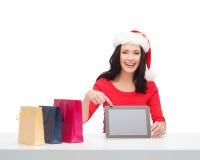 Mulher no chapéu do ajudante de Santa com PC da tabuleta Foto de Stock Royalty Free