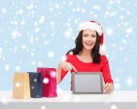 Mulher no chapéu do ajudante de Santa com PC da tabuleta Imagens de Stock Royalty Free