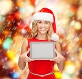 Mulher no chapéu do ajudante de Santa com PC da tabuleta Imagens de Stock