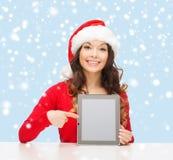Mulher no chapéu do ajudante de Santa com PC da tabuleta Fotos de Stock Royalty Free