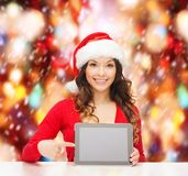 Mulher no chapéu do ajudante de Santa com PC da tabuleta Imagem de Stock