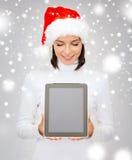 Mulher no chapéu do ajudante de Santa com PC da tabuleta Fotos de Stock