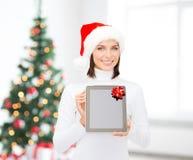 Mulher no chapéu do ajudante de Santa com PC da tabuleta Imagem de Stock Royalty Free