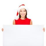 Mulher no chapéu do ajudante de Santa com placa branca vazia Fotografia de Stock