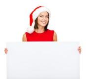 Mulher no chapéu do ajudante de Santa com placa branca vazia Fotos de Stock