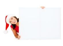Mulher no chapéu do ajudante de Santa com placa branca vazia Imagem de Stock Royalty Free