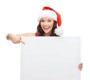 Mulher no chapéu do ajudante de Santa com placa branca vazia Imagens de Stock Royalty Free