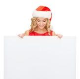 Mulher no chapéu do ajudante de Santa com placa branca vazia Foto de Stock
