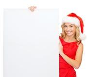 Mulher no chapéu do ajudante de Santa com placa branca vazia Fotos de Stock Royalty Free