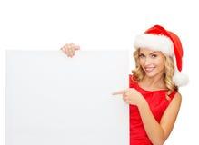 Mulher no chapéu do ajudante de Santa com placa branca vazia Foto de Stock Royalty Free