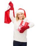 Mulher no chapéu do ajudante de Santa com sacos de compras Foto de Stock