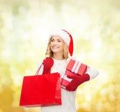 Mulher no chapéu do ajudante de Santa com sacos de compras Fotos de Stock Royalty Free