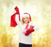 Mulher no chapéu do ajudante de Santa com sacos de compras Imagem de Stock Royalty Free