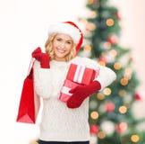 Mulher no chapéu do ajudante de Santa com sacos de compras Imagens de Stock