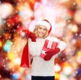 Mulher no chapéu do ajudante de Santa com sacos de compras Fotografia de Stock