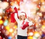 Mulher no chapéu do ajudante de Santa com sacos de compras Fotos de Stock