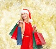 Mulher no chapéu do ajudante de Santa com sacos de compras Foto de Stock Royalty Free