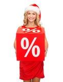Mulher no chapéu do ajudante de Santa com sinal vermelho da venda Fotos de Stock Royalty Free