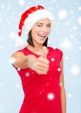 Mulher no chapéu do ajudante de Santa que mostra os polegares acima Foto de Stock