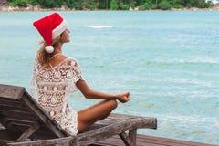 Mulher no chapéu do Natal que medita em uma pose da ioga na praia do thel fotografia de stock