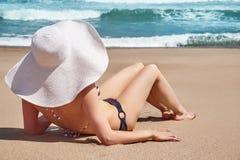 A mulher no chapéu encontra-se na areia branca na praia idílico A praia do oceano relaxa, viaja Imagens de Stock