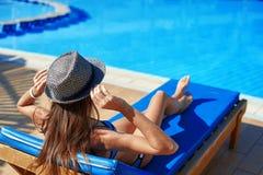 A mulher no chapéu que encontra-se em um vadio perto da piscina no hotel, horas de verão do conceito viajar relaxa fotos de stock