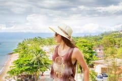 Mulher no chapéu que olha o horizonte, a praia e as árvores foto de stock royalty free