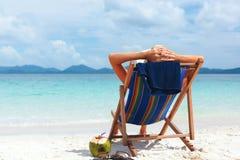 Mulher no chapéu que senta-se na praia tropical imagens de stock royalty free