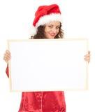 Mulher no chapéu vermelho de Santa com poster em branco Fotos de Stock Royalty Free