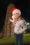 Mulher no chapéu de Santa que toma a foto da torre inclinada de Pisa, Itália Foto de Stock