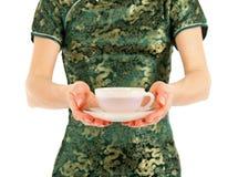 A mulher no chinês veste o oferecimento de um copo do chá Fotografia de Stock