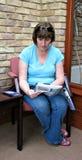 Mulher no compartimento da leitura da recepção foto de stock