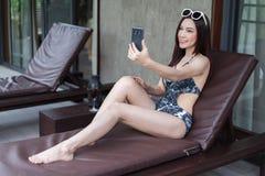 A mulher no deckchair e toma um selfie no telefone celular imagens de stock royalty free