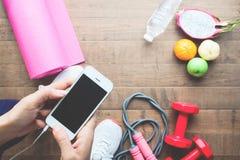 Mulher no desgaste do esporte usando o telefone celular com frutos e equipamentos de esporte no fundo fotografia de stock