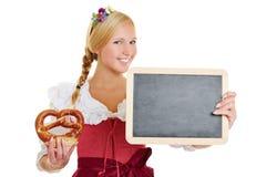 Mulher no dirndl com pretzel e quadro-negro Fotografia de Stock Royalty Free