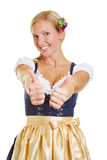 Mulher no dirndl que mantem dois polegares Fotografia de Stock