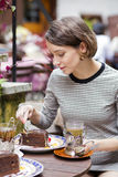 Mulher no envoltório do café o bolo com forquilha Imagem de Stock Royalty Free