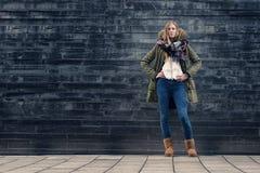Mulher no equipamento do inverno em Front Old Gray Wall fotografia de stock royalty free