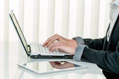 Mulher no escritório com COM do laptop Imagem de Stock Royalty Free