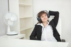 A mulher no escritório com fones de ouvido e escuta m Imagens de Stock