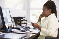 Mulher no escritório home usando o computador fotografia de stock royalty free