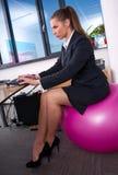 Mulher no escritório na esfera dos pilates fotografia de stock