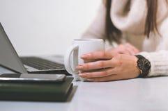 Mulher no escritório na frente do caderno que guarda um copo fotografia de stock