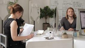 A mulher no escritório recolhe originais em uma pilha entre o pessoal na mesa filme